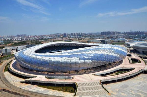大连市体育中心体育场位于大连市甘井子区西北路与岚岭路交会处。占地面积13.5万平方米,建筑面积12万平方米,6.1万个座位。体育场的室外两片训练场地占地60000平方米,能够承担田径、足球等奥运会赛事,同时兼顾城市大型活动功能。体育场造型为飘逸的曲线形态,体育场外观采用的ETFE气枕式膜结构面积是目前世界上仅次于北京水立方的大型单体ETFE膜结构建筑。 场馆采用由ETFE(聚四氟乙烯和乙烯共聚物)制成的气枕组合而成。选用了透明色、乳白色、天蓝色等几种不同颜色的ETFE膜材的拼色设计。气枕的施工安装极其繁